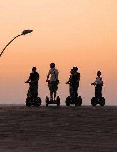 Fem personer som åker segway i solnedgång