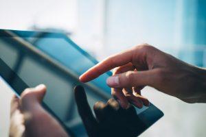 en hand som pekar på en Ipad skärm