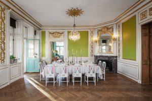 Stor salong med guldiga detaljer och gröna väggar