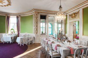 Stor salong med gröna väggar och guldiga detaljer
