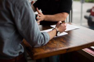 Två personers armar som skriver och gör gester som att dem kommunicerar med varann