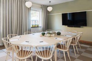 Stort beige bord med stolar och tv