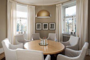 Runt bord med stolar i ett beige rum