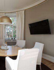 Tv och runt bord med stolar i ett beige rum