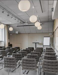 Rum med gråa stolar uppradade framför ett litet whiteboard