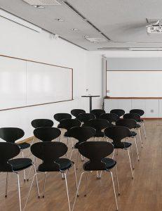 Stort vitt rum med whiteboards på väggarna och svarta stolar uppradade