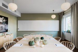 Stort beige bord med stolar och stort whiteboard