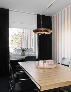 Bord med stolar framför ett fönster i ett litet rum med rosa-randiga väggar