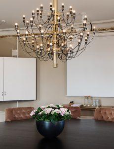 Svart bord med rosa fåtöljer och stor guld lampa ovanför