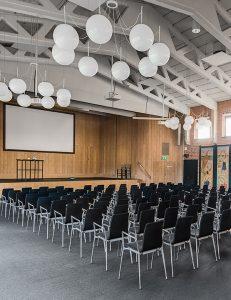 Stor sal med stolar uppradade framför en scen