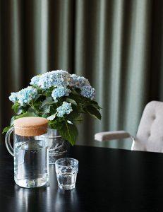 Detaljbild på blommor, vatten, stol och grön bakgrund