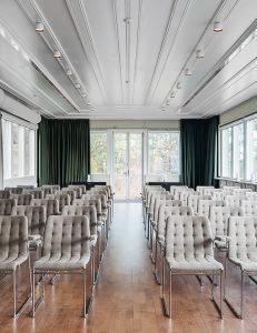 Stort rum med gråa stolar uppradade fram whiteboard och stora fönster med havsutsikt
