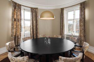 Stort svart bord med blommig-mönstrade stolar och gardiner