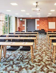 Rader av bord och stolar i ett rum med varma toner och stora fönster ut mot hav