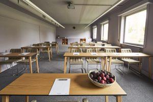 Rum med gråa stolar uppradade framför ett whiteboard