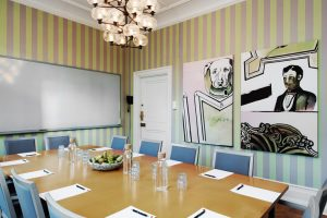 Mellanstort rum med grön-rosarandiga väggar med konst tavlor