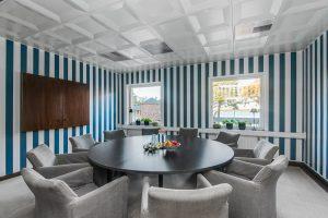 Stort svart bord med gråa stolar och blå-vitrandiga väggar