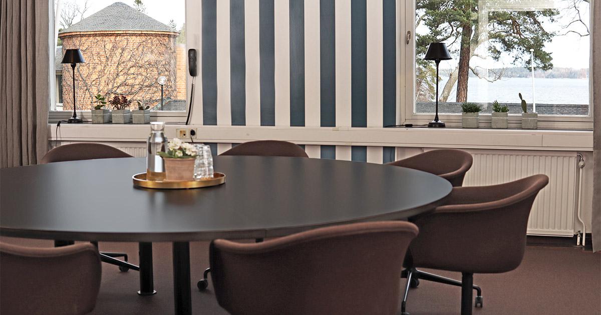 konferenslokal med runt bord och randiga tapeter