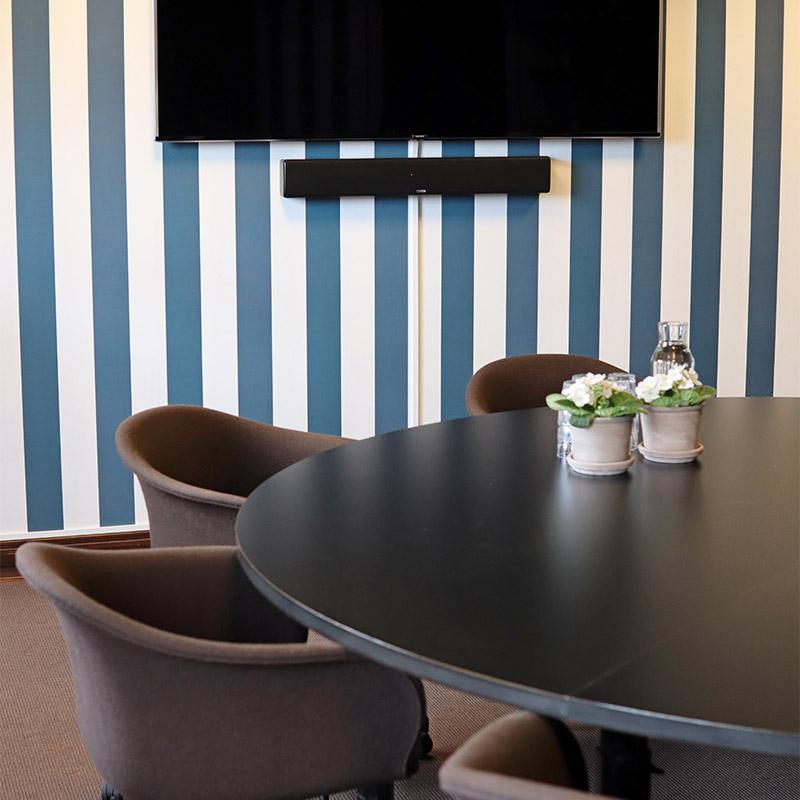 mötesrum med tv, runt bord och randiga tapeter