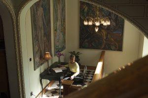 Hall med stora tavlor och en kvinna som sitter med en bok
