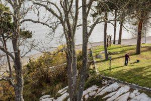 Trädgårdsmästaren samlar löv ute på gården med havet som bakgrund