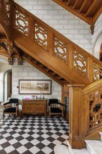 Hall med en stor trappa och svart-vit rutigt golv