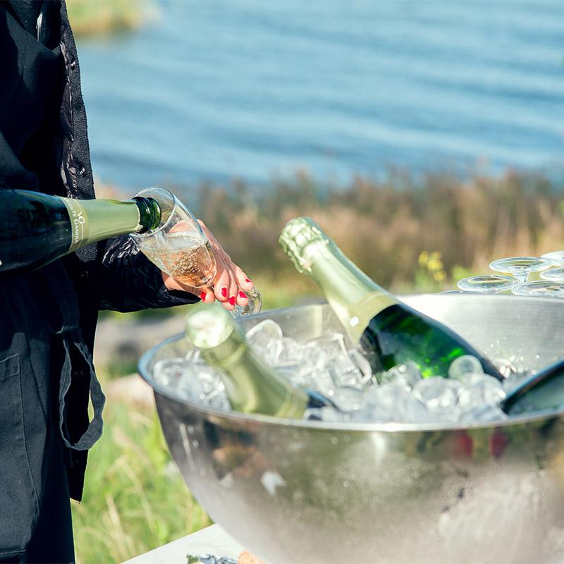 servitör som häller upp bubbel utomhus vid havet