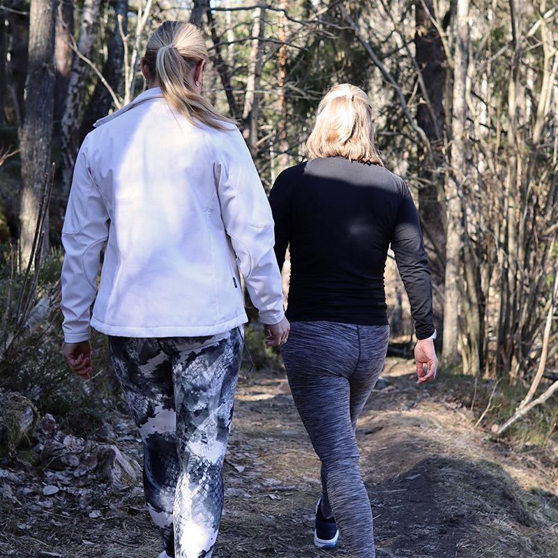två kvinnor på promenad i skogen