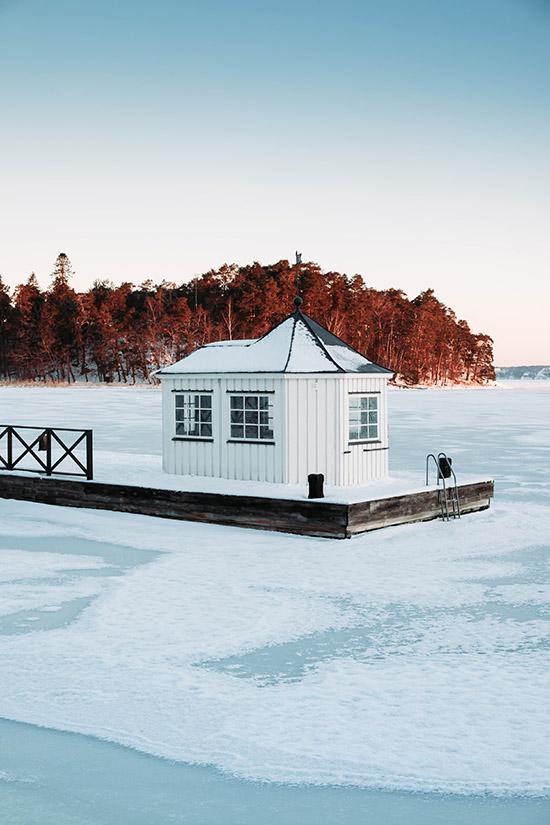 Brygga med lust hus på frusen sjö
