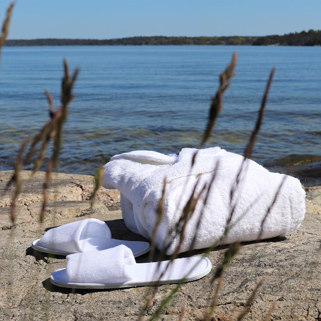 badrock och tofflor hopvikta på en sten vid havet