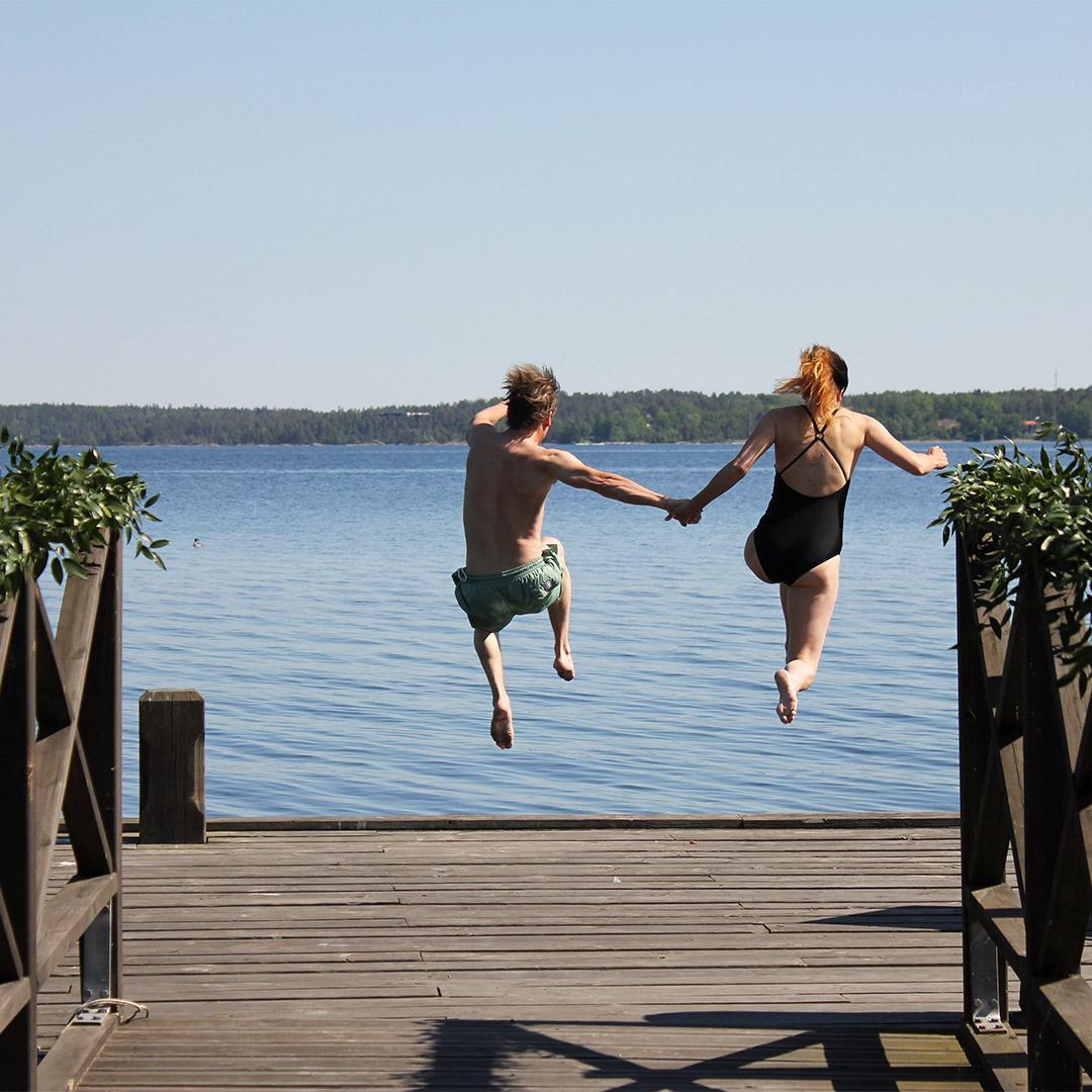 par som hoppar från brygga hand i hand