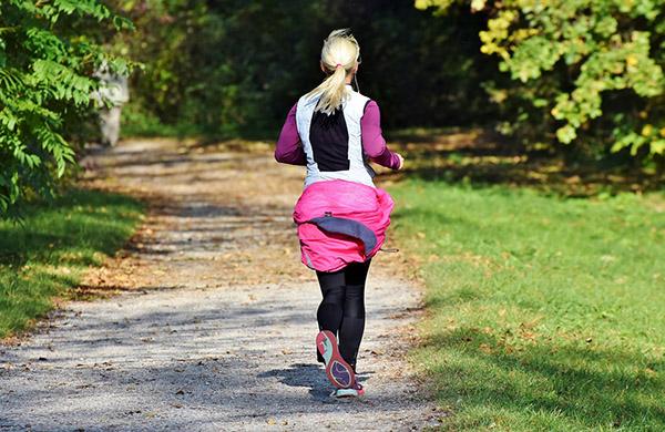 kvinna som joggar på gångväg