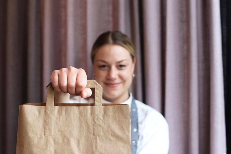 bild på tjej som håller upp en papperskasse