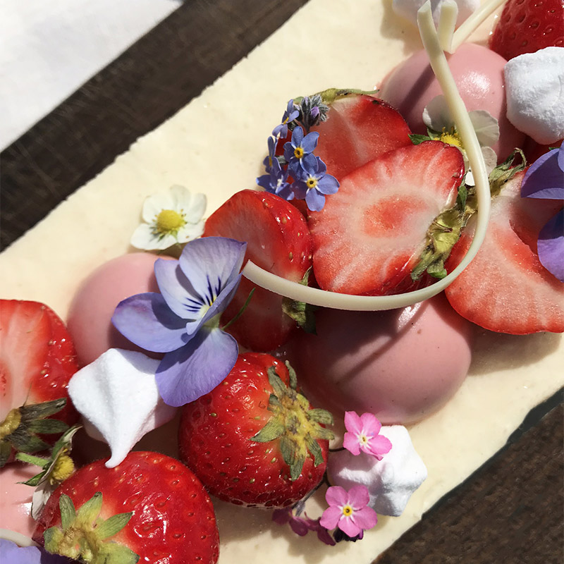 tårta med jordgubbar, blommor och vit choklad