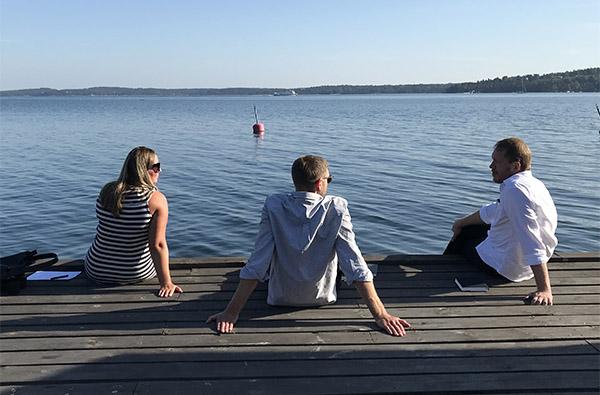 tre personer sitter på en brygga