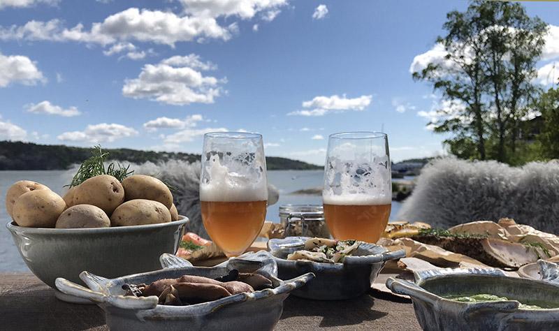 Sillunch med potatis och öl serverad på brygga