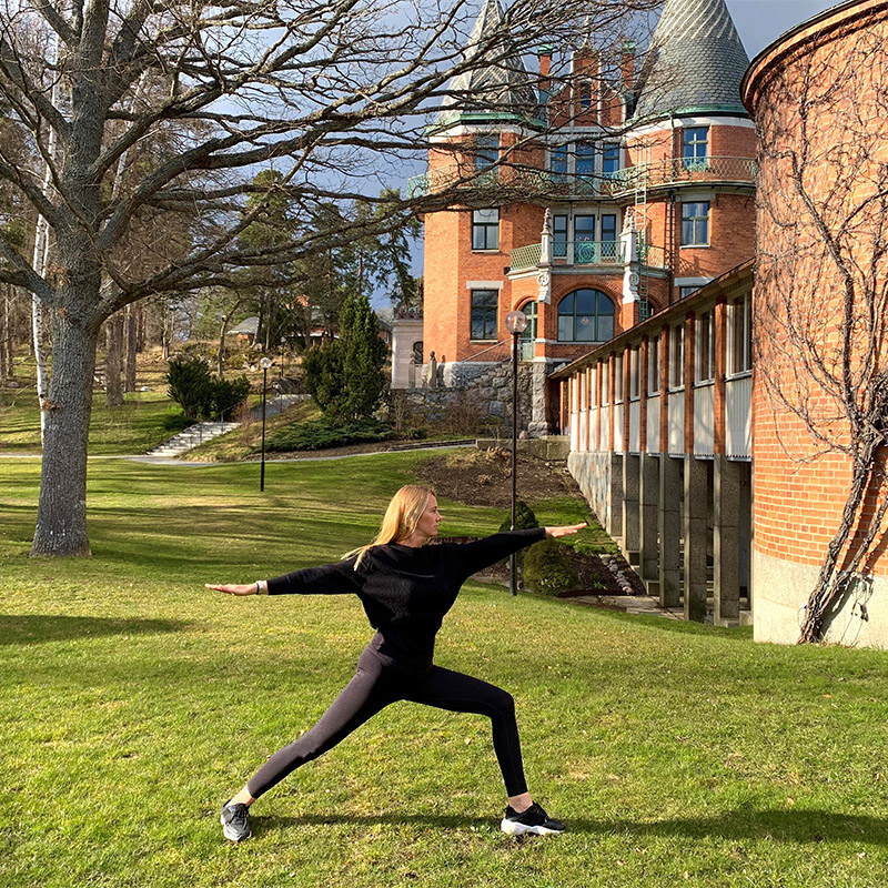 Kvinna utför yoga på gräsmatta