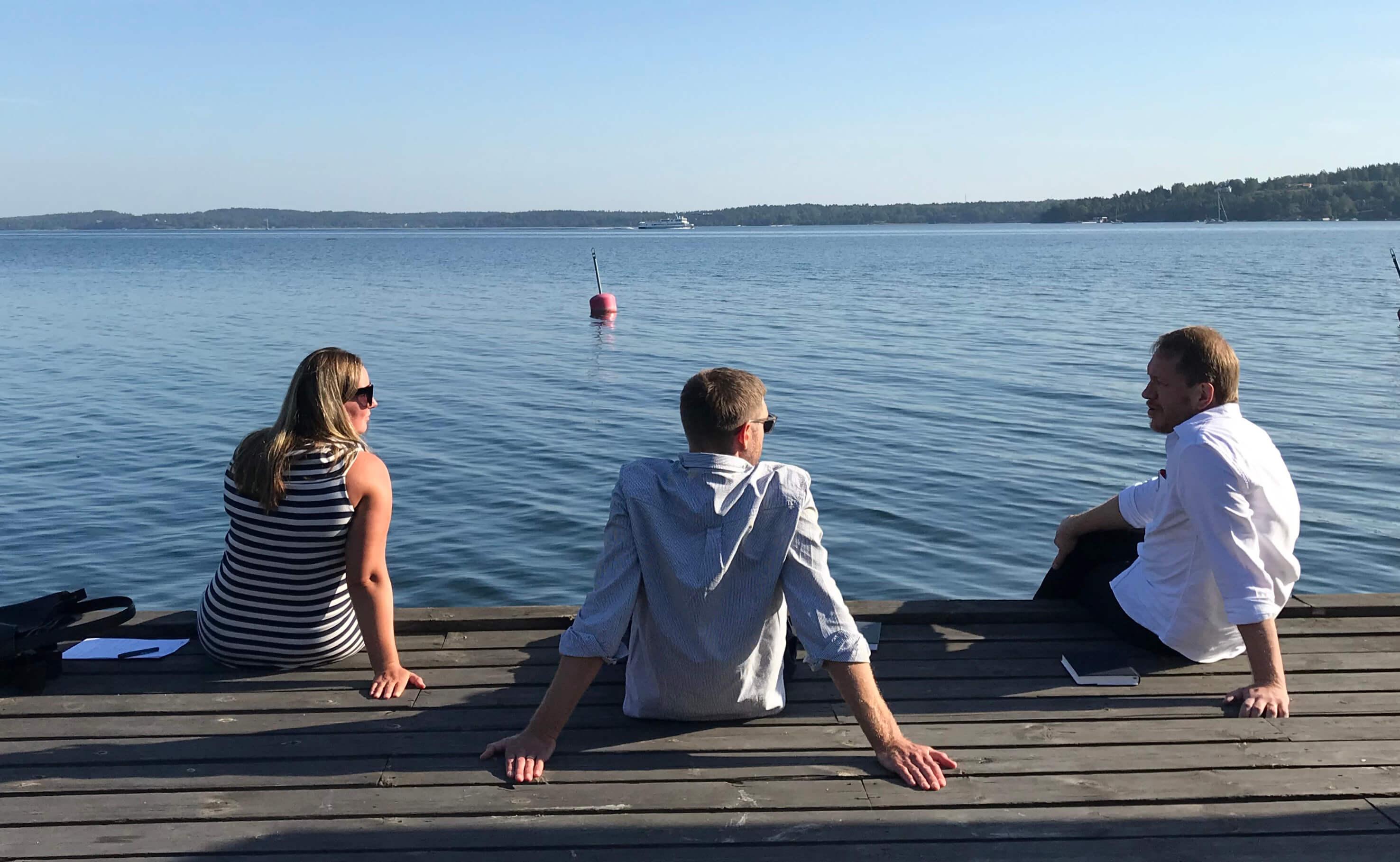 tre personer som sitter på en brygga
