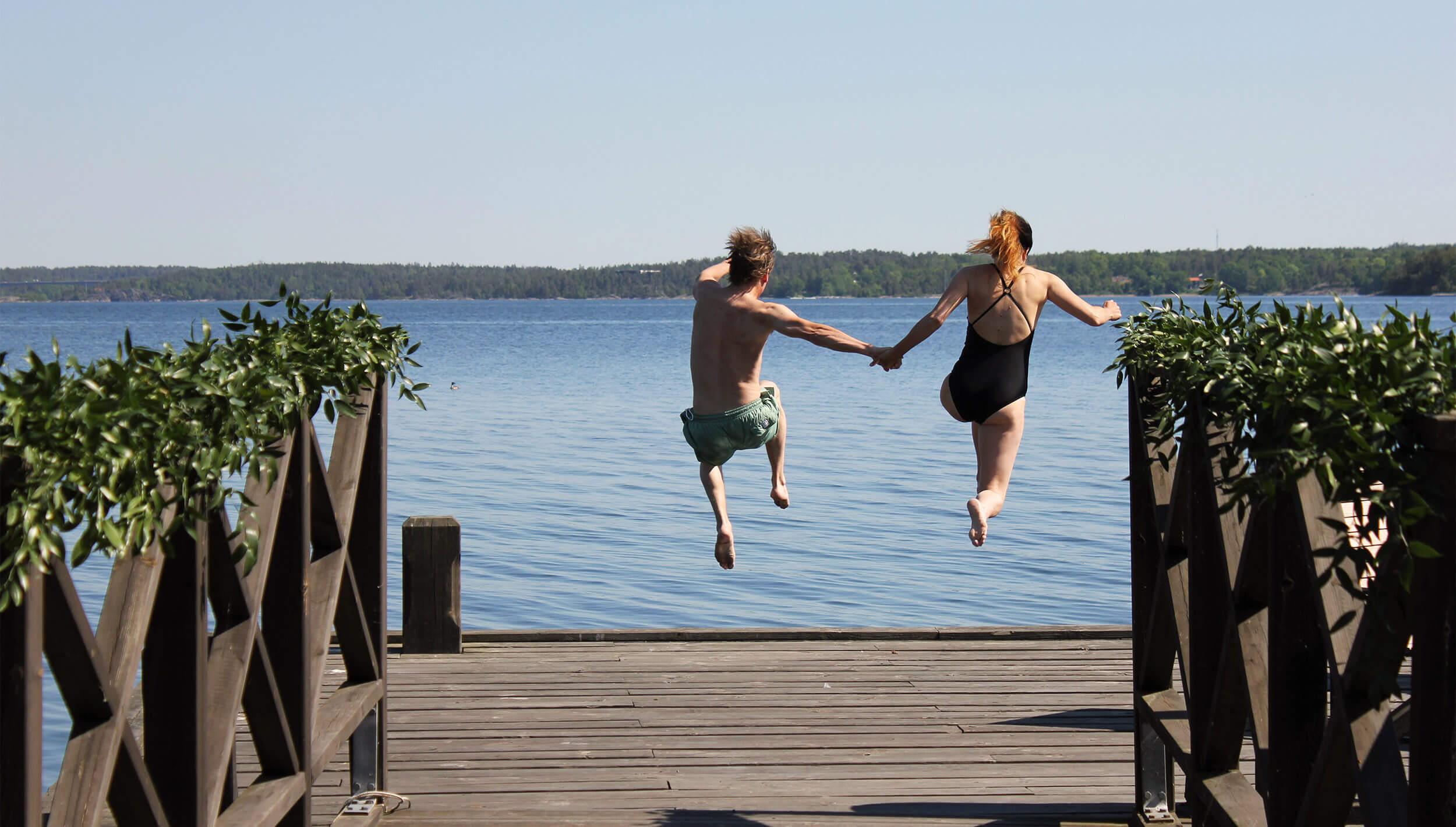 Par som hoppar från brygga ner i havet