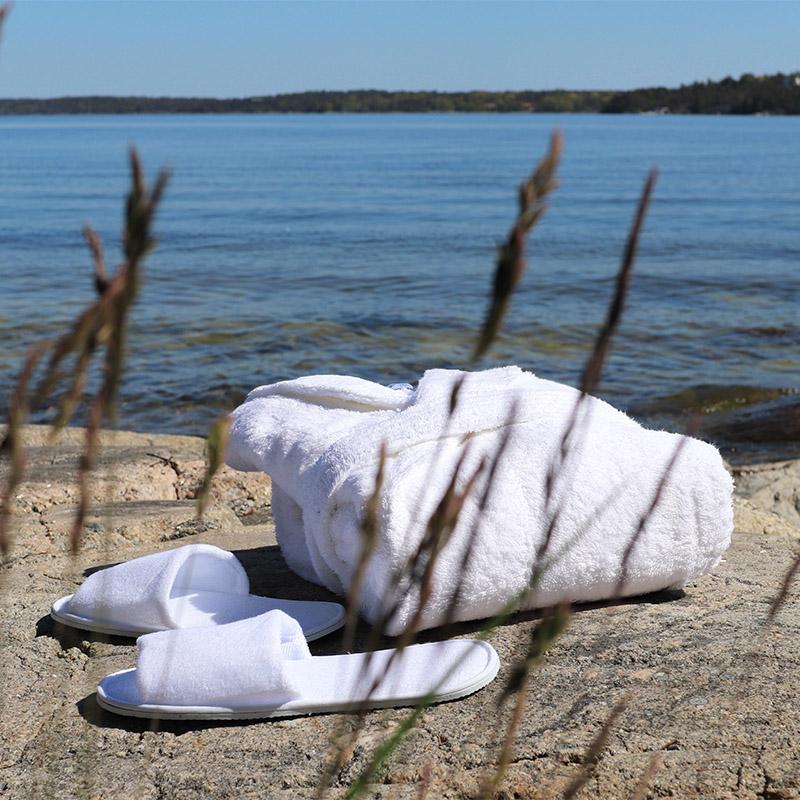 badhandduk och tofflor på sten vid havet