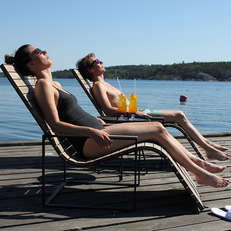 Par som solar på brygga sittandes i två solstolar