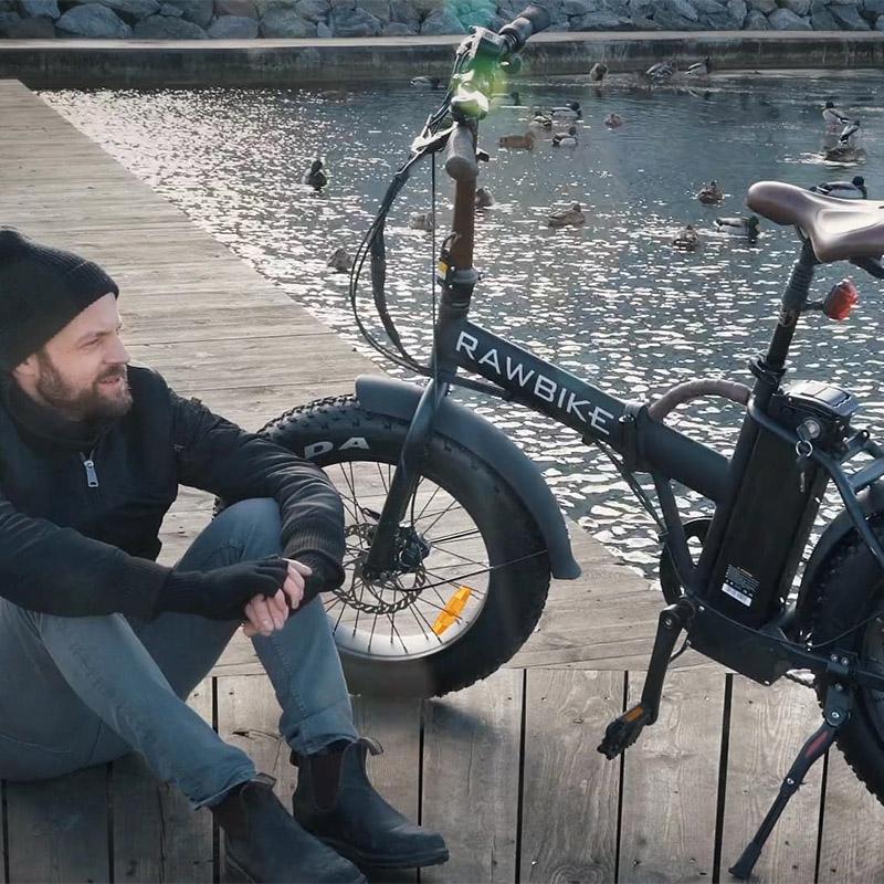 man som sitter på en brygga bredvid sin elcykel