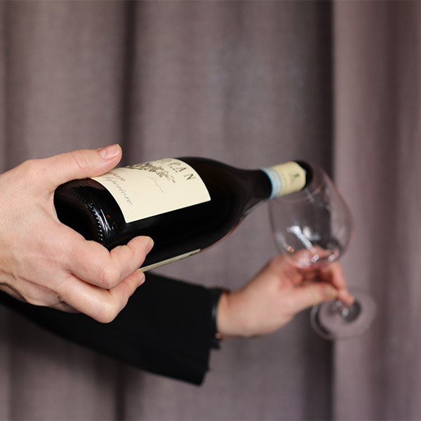 servitör som häller upp rödvin i ett glas