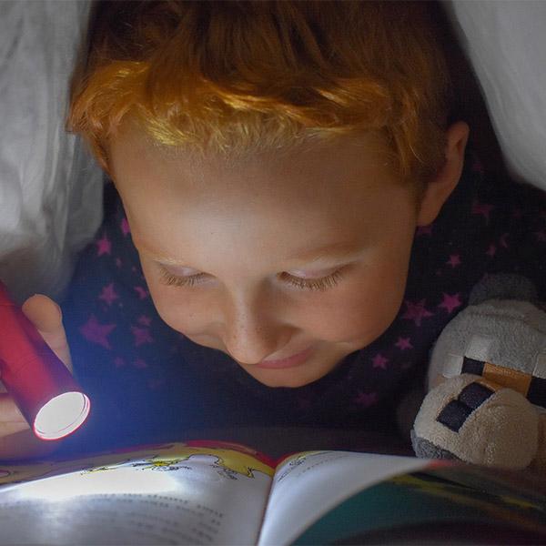 pojke som läser en bok med ficklampa under täcket