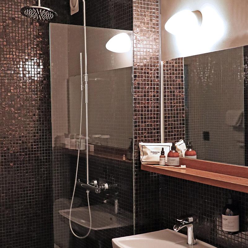 badrum på hotellrum med dusch och brun mosaik