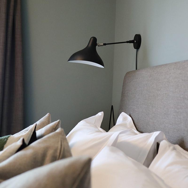 hotellsäng med många kuddar och svart sänglampa