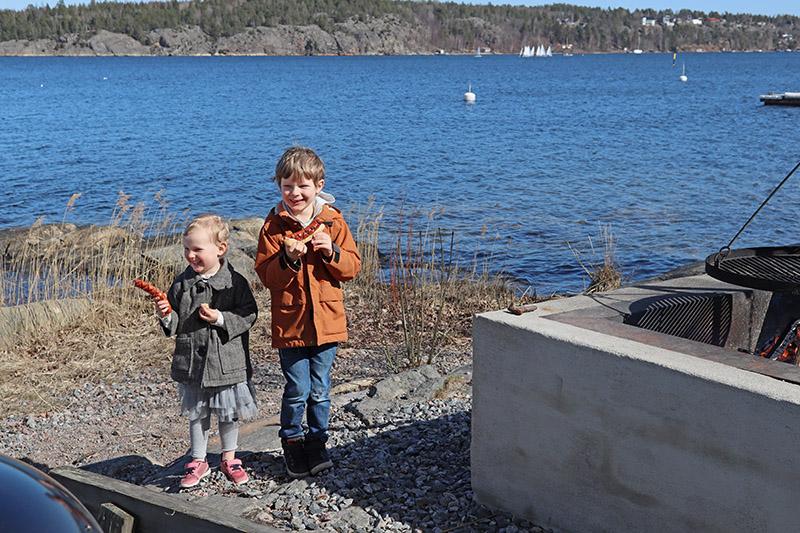 två barn som äter korv och bröd vig grillplats vid havet