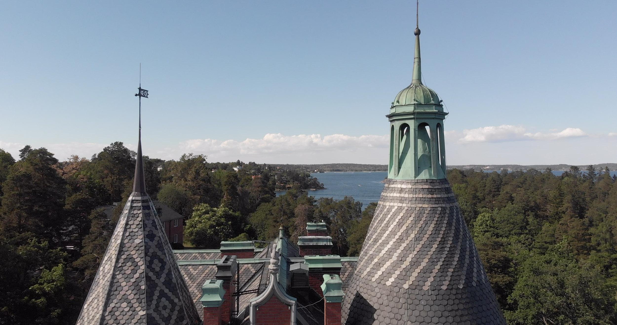 Tinnar och torn på sekelskiftsvilla med hav i bakgrunden
