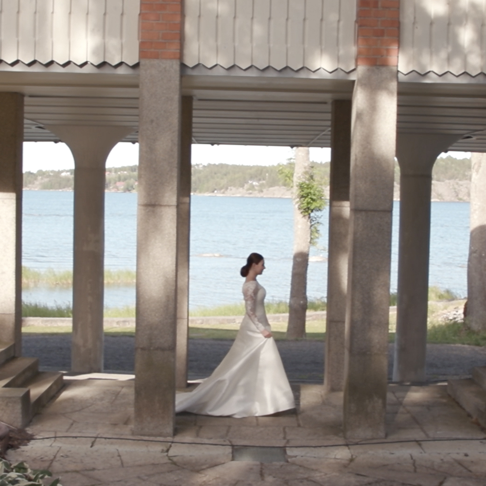 Kvinna i brudklänning utomhus vid havet