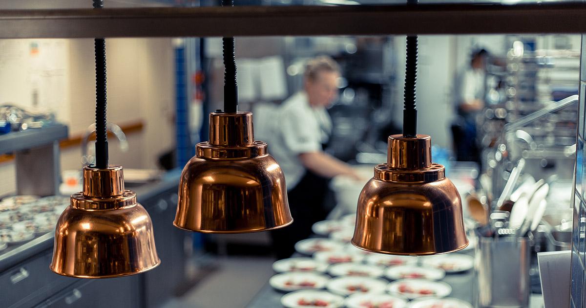 restaurangkök med värmelampor i koppar